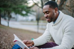 Man reading a book sat on a park bench